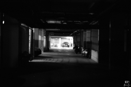 Light at the end of a dark corridor in a basement parking lot.