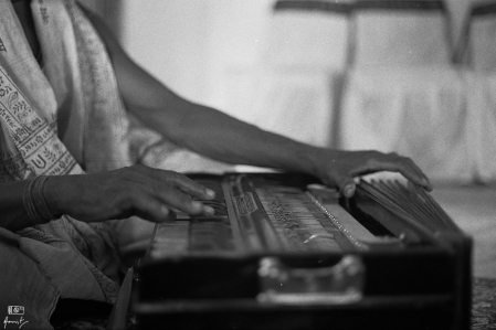 A musician of Sankirtan playing the harmonium. Sankirtan groups go around singing the praise of Lord Vishnu in rural Odisha. A harmonium is a pump type music organ.