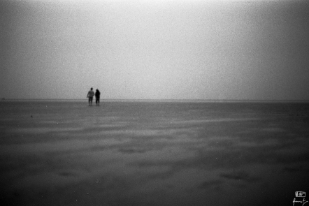 A couple on an evening stroll on the sea bed in Chandipur in Odisha, India. Chandipur is famous for the vanishing beach. One can walk for kilometers into the sea during low tides.